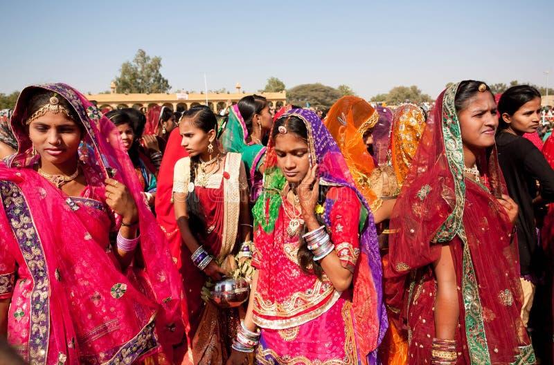 Härliga kvinnor i den röda sari som går till och med folkmassan royaltyfri foto