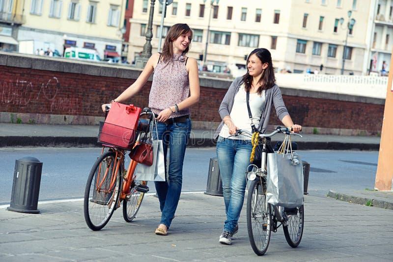 Härliga kvinnor i staden med cyklar och påsar arkivbild