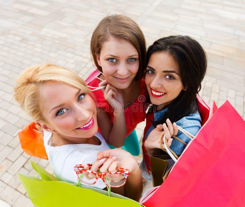 Härliga kvinnor med deras shoppingpåsar royaltyfria bilder
