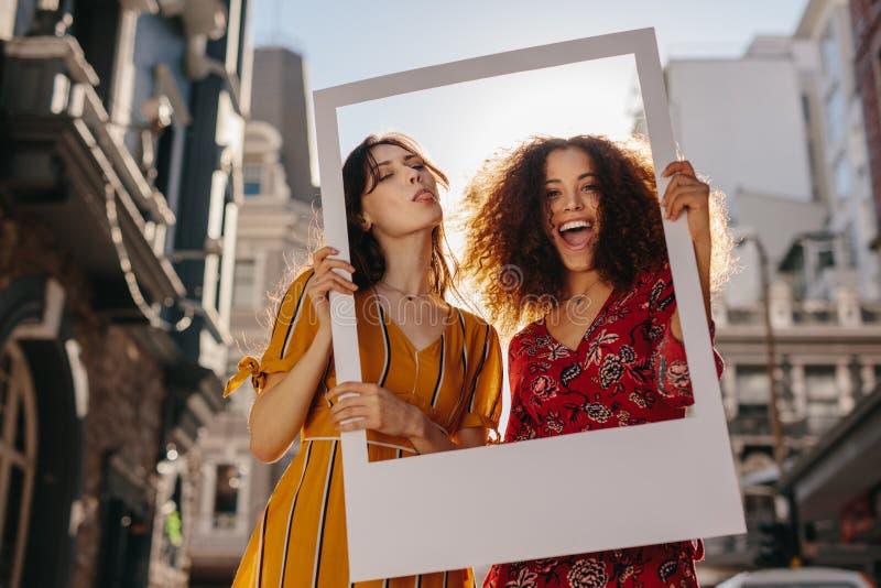 Härliga kvinnor med en tom fotoram arkivbild
