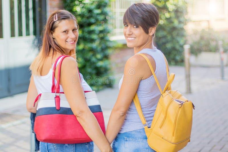 Härliga kvinnor med en trendig påse som går i gatan arkivfoton