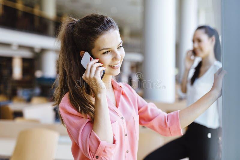 Härliga kvinnor som använder telefoner och talkin under avbrott royaltyfri bild