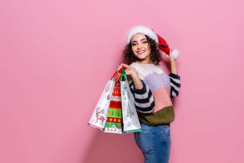 Härliga kvinnor som bär ljus jul som bär färgrika shoppa påsar På rosa bakgrund Julshopping och royaltyfria foton