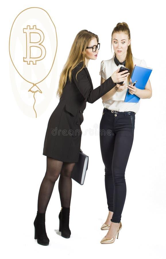 Härliga kvinnor som står över vit bakgrund med bitcoin, skissar och samtal Faktiskt pengarbegrepp Cryptocurrency royaltyfri fotografi