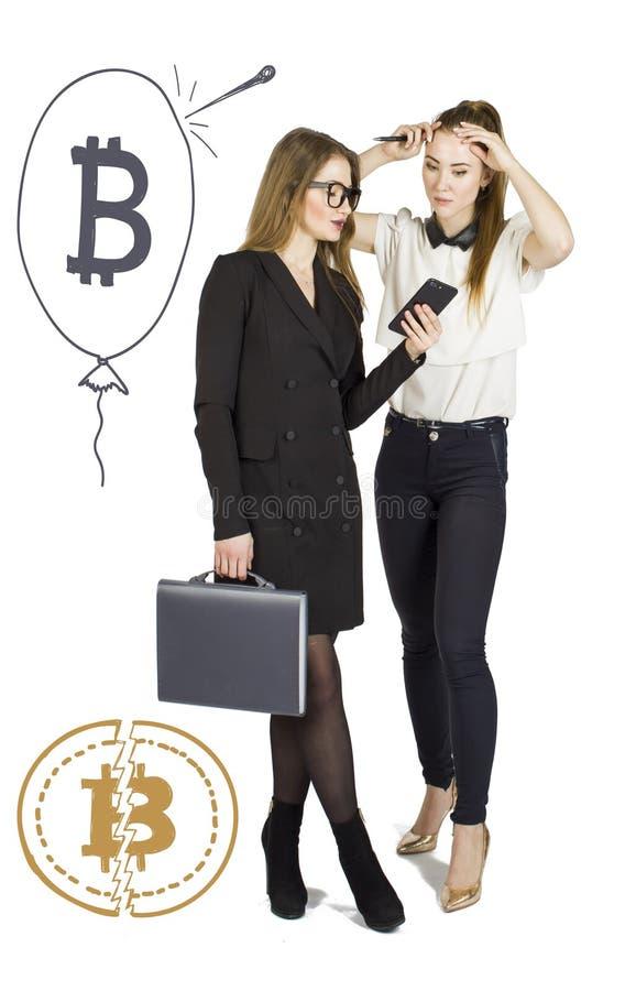 Härliga kvinnor som står över vit bakgrund med bitcoin, skissar och samtal Faktiskt pengarbegrepp Cryptocurrency royaltyfria bilder