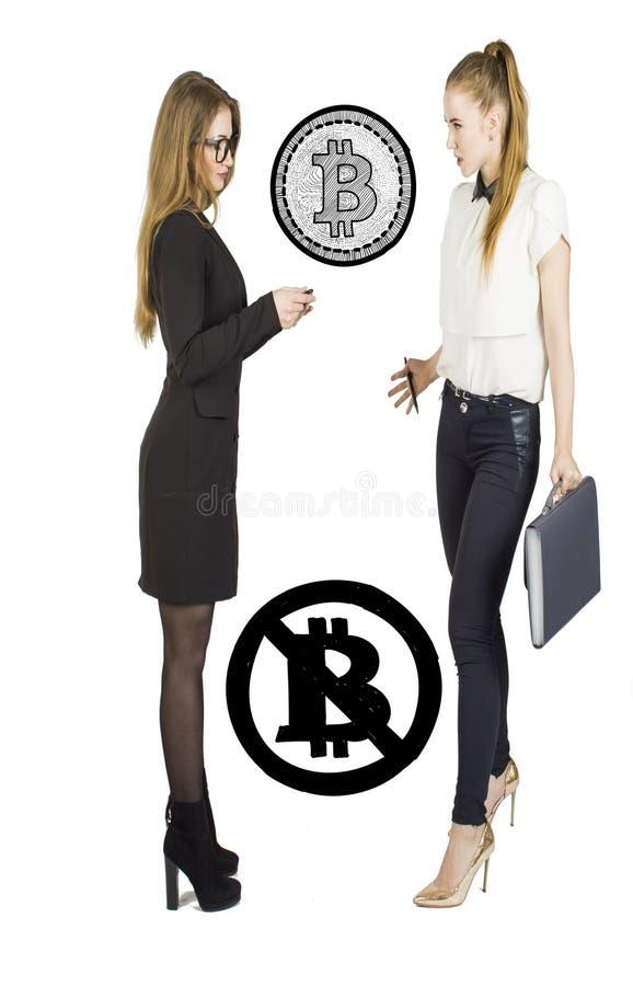 Härliga kvinnor som står över vit bakgrund med bitcoin, skissar och samtal Faktiskt pengarbegrepp Cryptocurrency arkivbild
