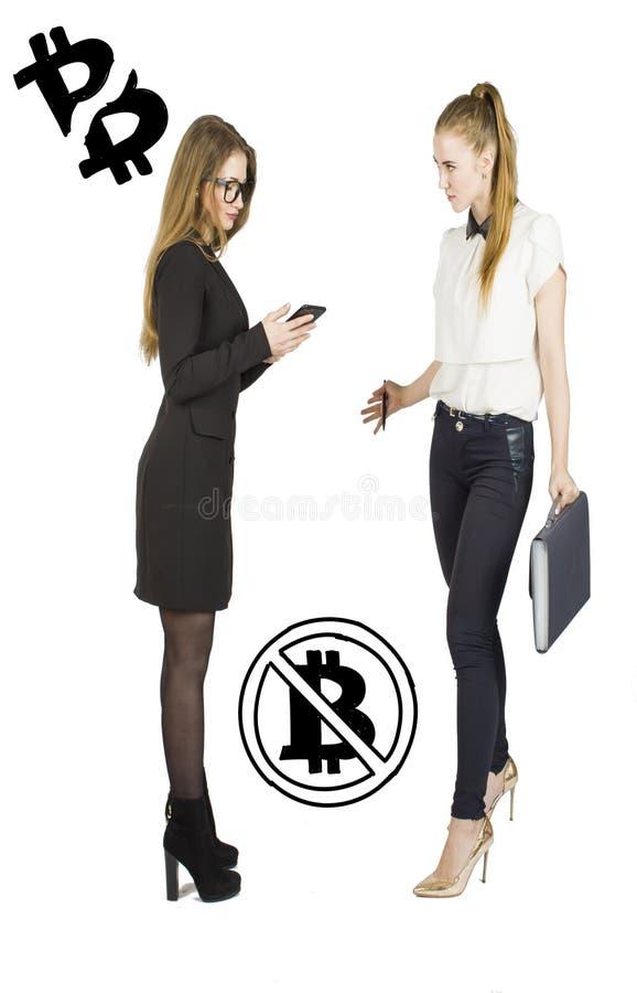 Härliga kvinnor som står över vit bakgrund med bitcoin, skissar och samtal Faktiskt pengarbegrepp Cryptocurrency arkivfoto