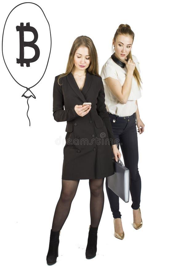 Härliga kvinnor som står över vit bakgrund med bitcoin, skissar och samtal Faktiskt pengarbegrepp Cryptocurrency royaltyfria foton