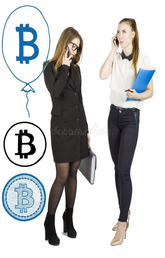 Härliga kvinnor som står över vit bakgrund med bitcoin, skissar och samtal Faktiskt pengarbegrepp Cryptocurrency royaltyfri bild