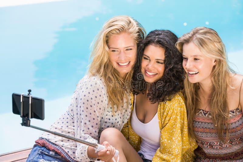 Härliga kvinnor som tar en selfie av simbassängen arkivbild