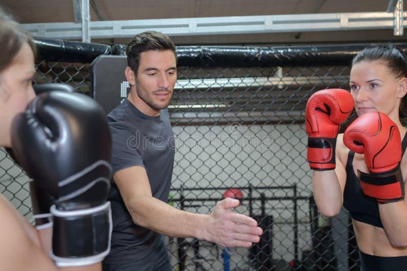 Härliga kvinnor som utbildar hård boxning i idrottshall royaltyfria foton