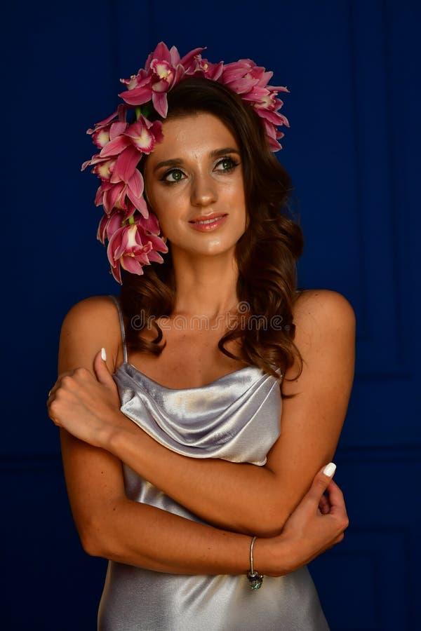 Härliga kvinnor under vit skyler och röda blommor på hennes huvud och stora ögon royaltyfri foto