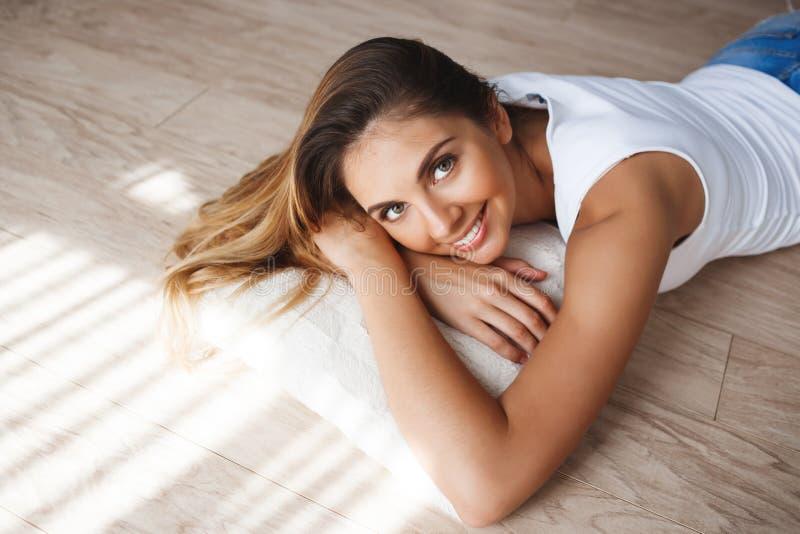 Härliga le kortslutningar för skjorta och för grov bomullstvill för iklädd vit för ung kvinna som ligger på golv arkivbild