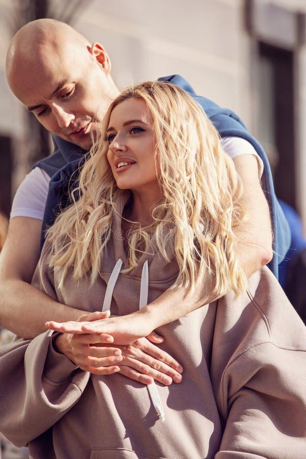Härliga le lyckliga par som kramar med förälskelse och trycker sig på till händerna på centrumbakgrund i modehoodie arkivbild