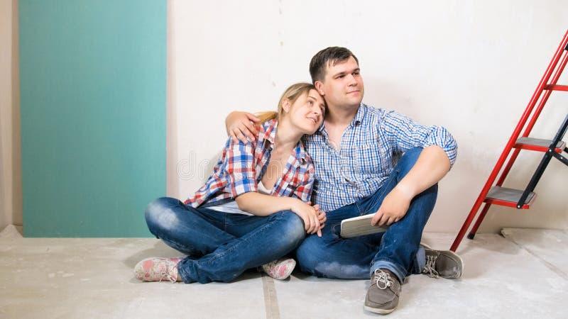 Härliga le par som kramar i nytt hus under konstruktion royaltyfri foto