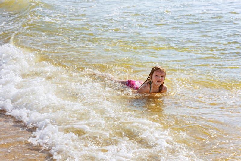 härliga liten flickabad i havet royaltyfri foto
