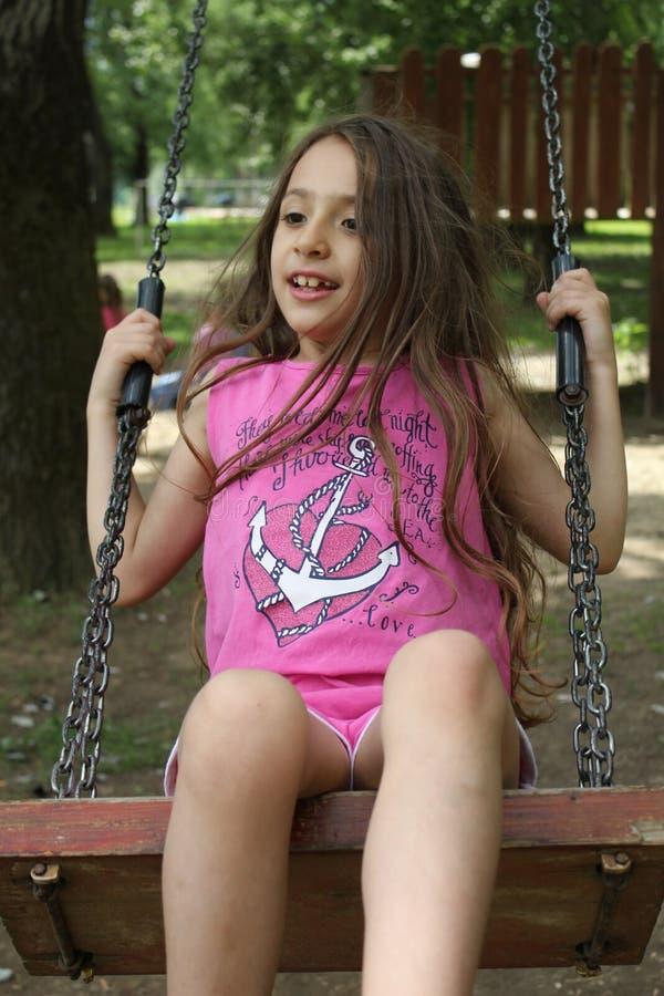 Härliga liten flickagungor på gungan royaltyfri fotografi