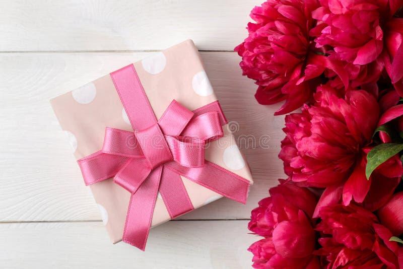 Härliga ljusa rosa blommapioner och gåvaask på en vit träbakgrund Top besk?dar arkivfoto