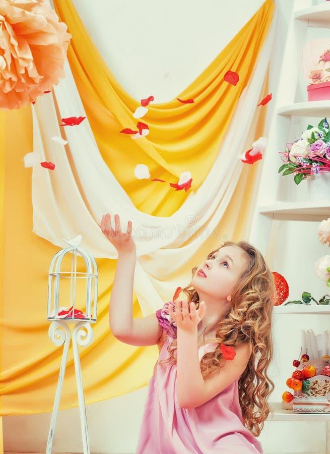 Härliga lockig-haired flickalekar med kronblad royaltyfri fotografi