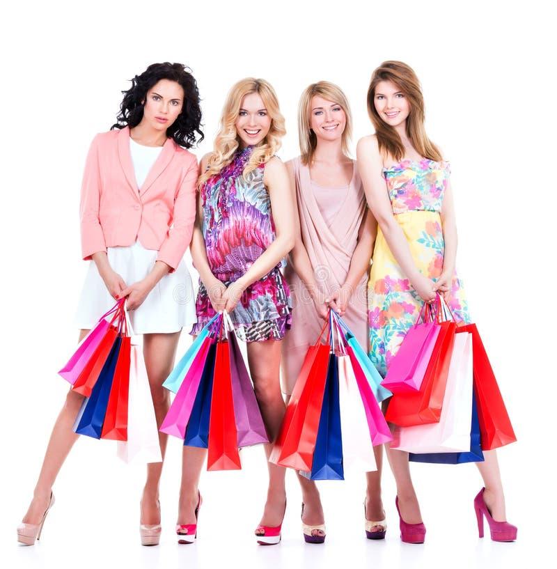 Härliga lyckliga kvinnor med flerfärgade shoppingpåsar arkivfoto