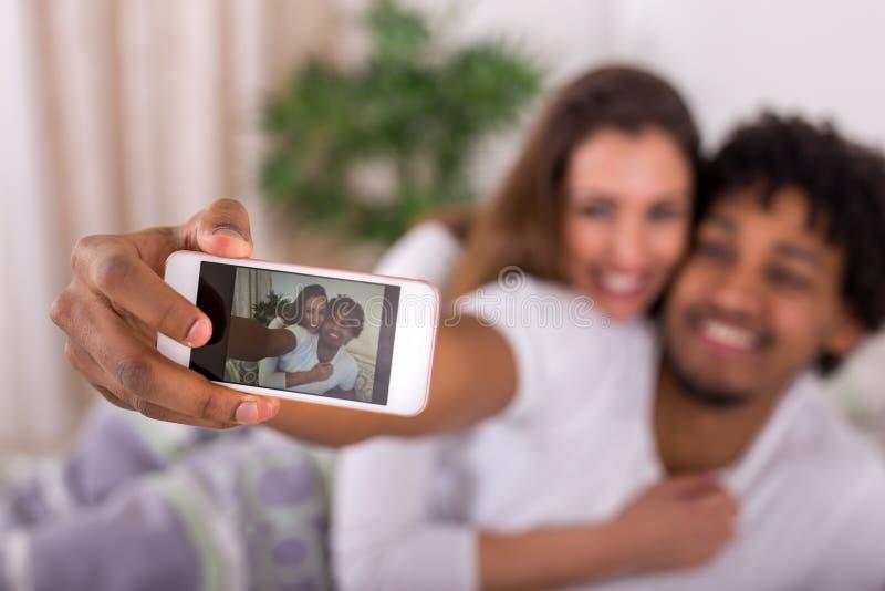 Härliga lyckliga par som upp vaknar och tar en selfie i bedren royaltyfria bilder