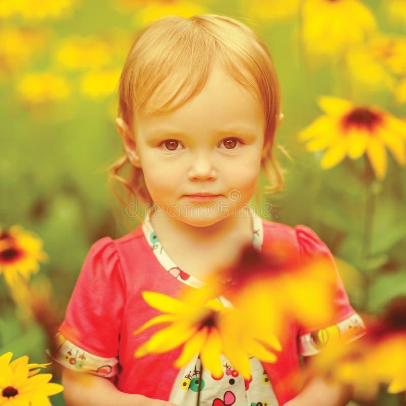 Härliga lyckliga små behandla som ett barn flickasammanträde på en grön äng med arkivfoton