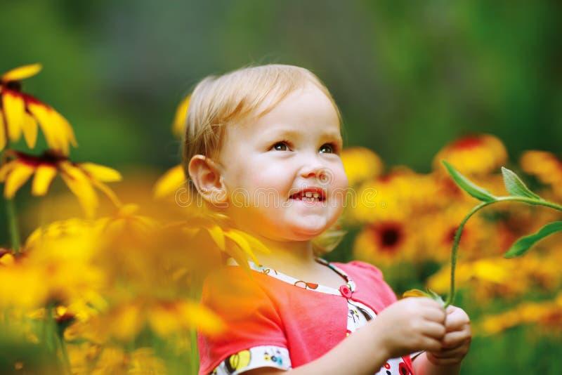 Härliga lyckliga små behandla som ett barn flickasammanträde på en grön äng med arkivbilder