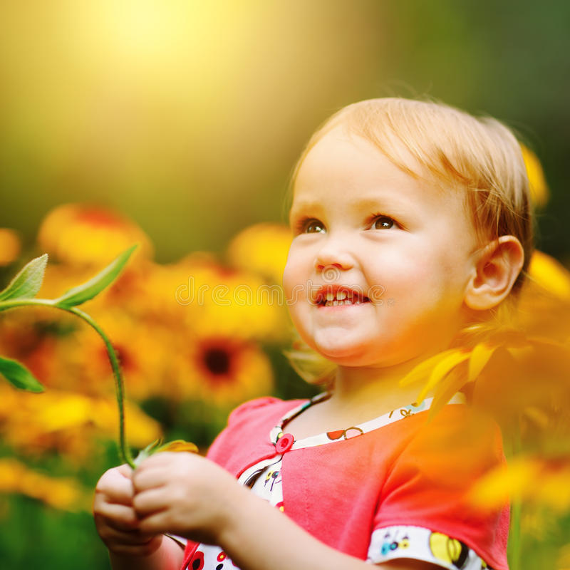 Härliga lyckliga små behandla som ett barn flickasammanträde på en grön äng med royaltyfri fotografi