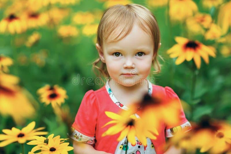 Härliga lyckliga små behandla som ett barn flickasammanträde på en grön äng med arkivfoto