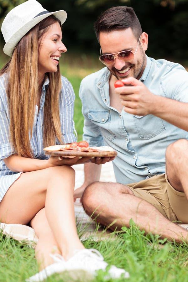 Härliga lyckliga unga par som tillsammans tycker om deras tid och att ha att koppla av picknicken i, parkerar royaltyfria bilder