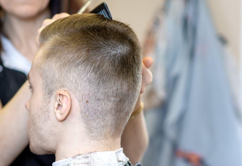 Härliga mäns frisyr och frisyr i barberaren shoppar Sammantr?de f?r ung man i en stol royaltyfri bild