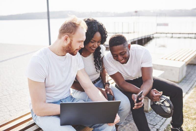 Härliga mång- etniska vänner som använder en bärbar dator i gatan Ungdomlivsstilbegrepp royaltyfri foto