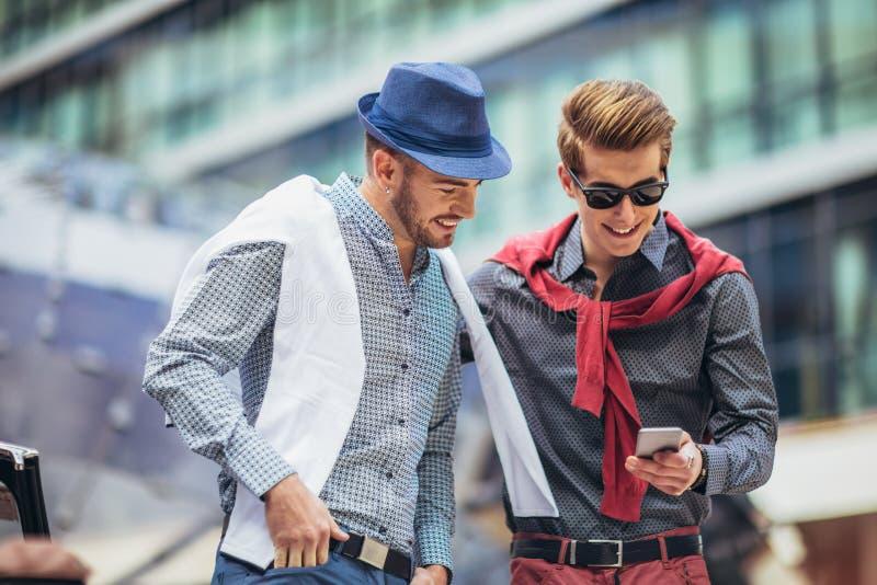 Härliga modeller som använder utomhus telefonen, stadsstilmode royaltyfria foton
