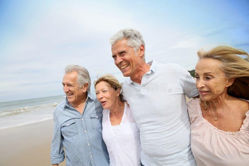 Härliga moderiktiga pensionärer som går på beacdhen arkivbild