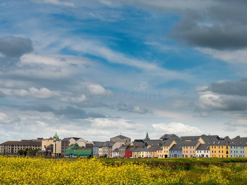 Härliga moln över den Galway staden, gula blommor i förgrund, söder parkerar, Claddaghen, den varma soliga dagen, rika färger fotografering för bildbyråer