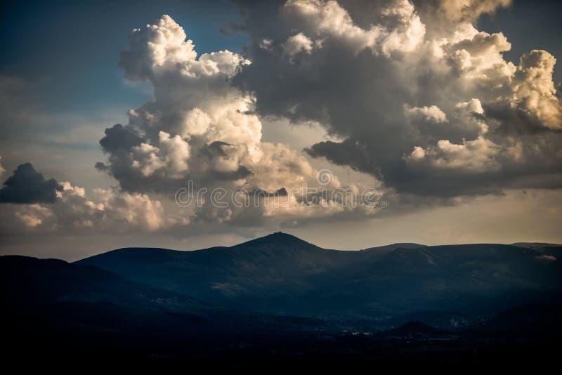 Härliga moln med solen som tränger igenom dem under solnedgångove arkivbild