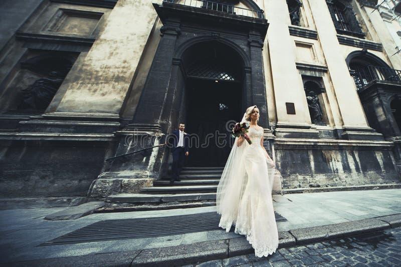 Härliga nygift personpar som poserar nära den gamla kyrkan, elegant brud arkivbild