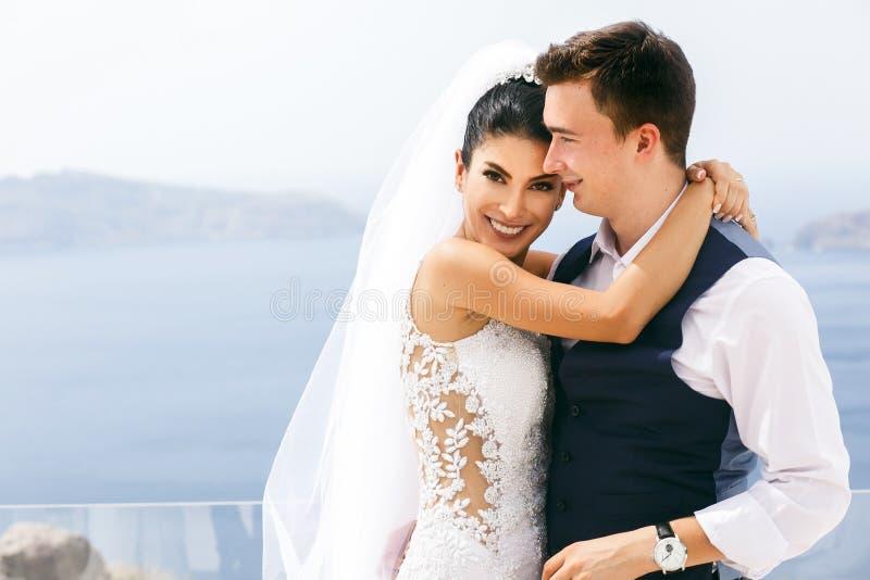 Härliga nygifta personer som kramar på havet royaltyfria bilder