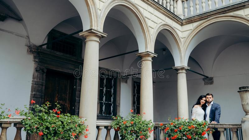 Härliga nygifta personer tycker om sikten, medan stå på den gamla balkongen som dekoreras med röda blommor Det ursnyggt royaltyfria foton