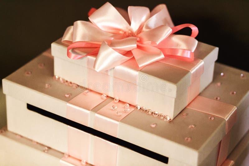 Härliga och eleganta bröllopgåvor i vita askar med det rosa stödet arkivbilder