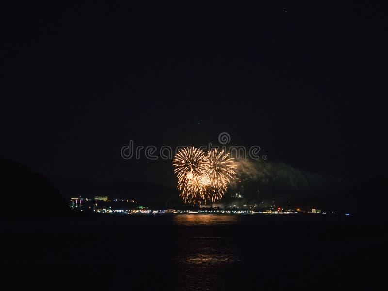 Härliga och färgrika fyrverkerier över stad på natten över floden royaltyfria foton