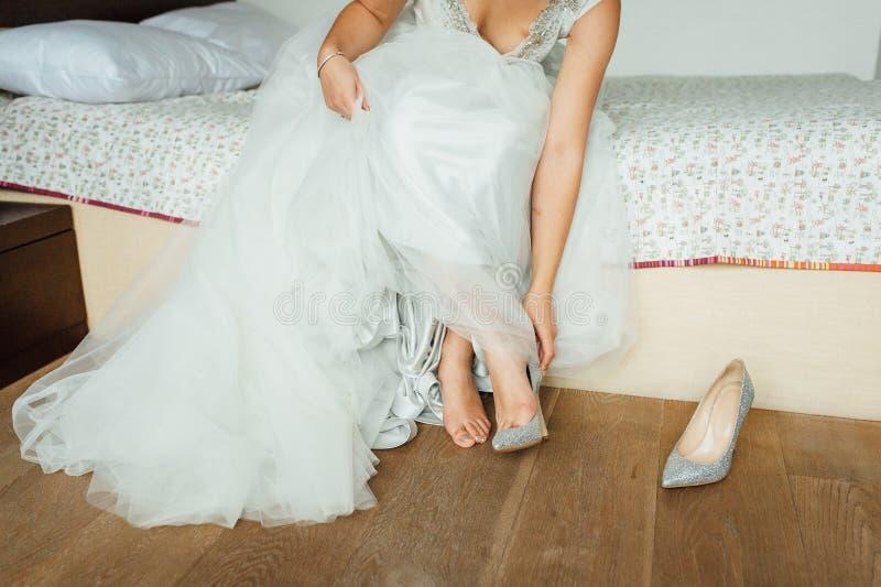 Härliga och idrotts- ben av bruden, i att gifta sig skor royaltyfri foto