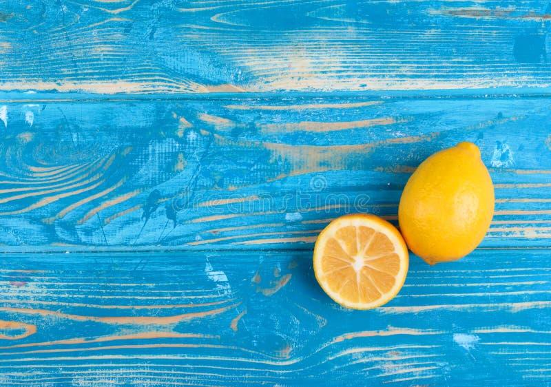 Härliga och mogna citroner på en blå trätabell fotografering för bildbyråer
