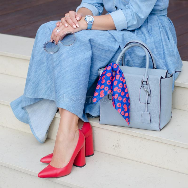 Härliga och trendiga skor på kvinna` s lägger benen på ryggen Kvinna Stilfull damtillbehör röda skor, blå påse, grov bomullstvill royaltyfri fotografi