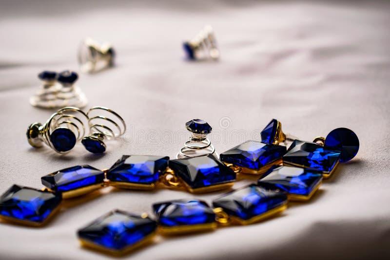 Härliga och trendiga smycken och tillbehör för kvinnor Safirörhängen med fyrkantiga stenar på vit textilbakgrund Blått arkivfoto