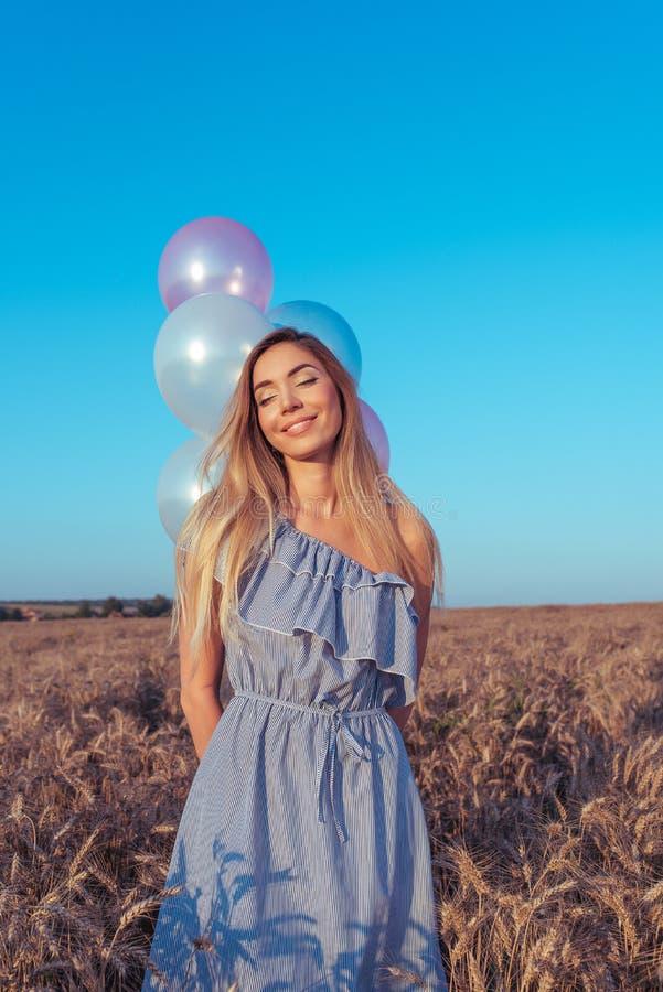Härliga och ung flickaställningar i sommaren i ett vetefält I hans hand färgade ballonger Sinnesrörelser av lugna leendeglädje arkivfoto