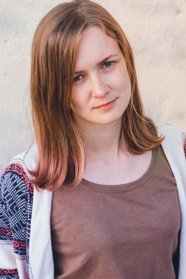 Härliga och ung flickaställningar på en neutral bakgrund fotografering för bildbyråer