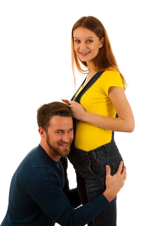 Härliga par - anseende för ung man som och gravid kvinnaisoleras över vit royaltyfri bild