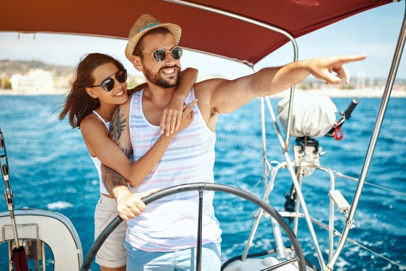 Härliga par av vänner som seglar på ett fartyg och att tycka om ljus solig dag royaltyfri foto