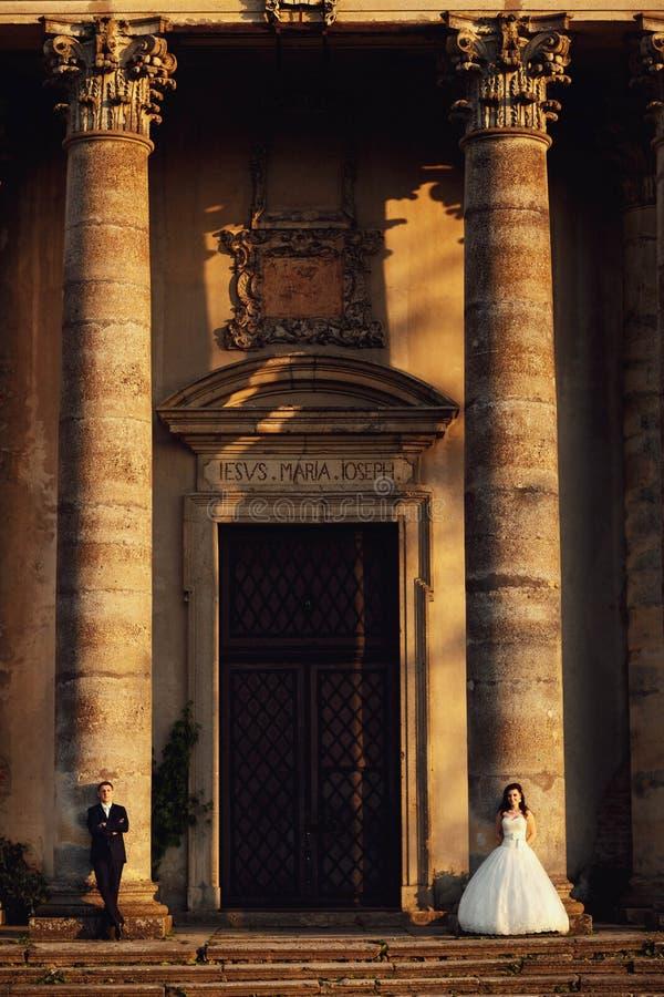 Härliga par i bröllopsklänning utomhus nära tappningportalingången med kolonner arkivbild